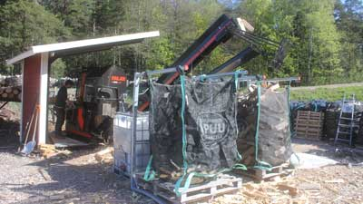 Från vedmaskines löpband faller klabbarna i 1,5 m3 säckar.